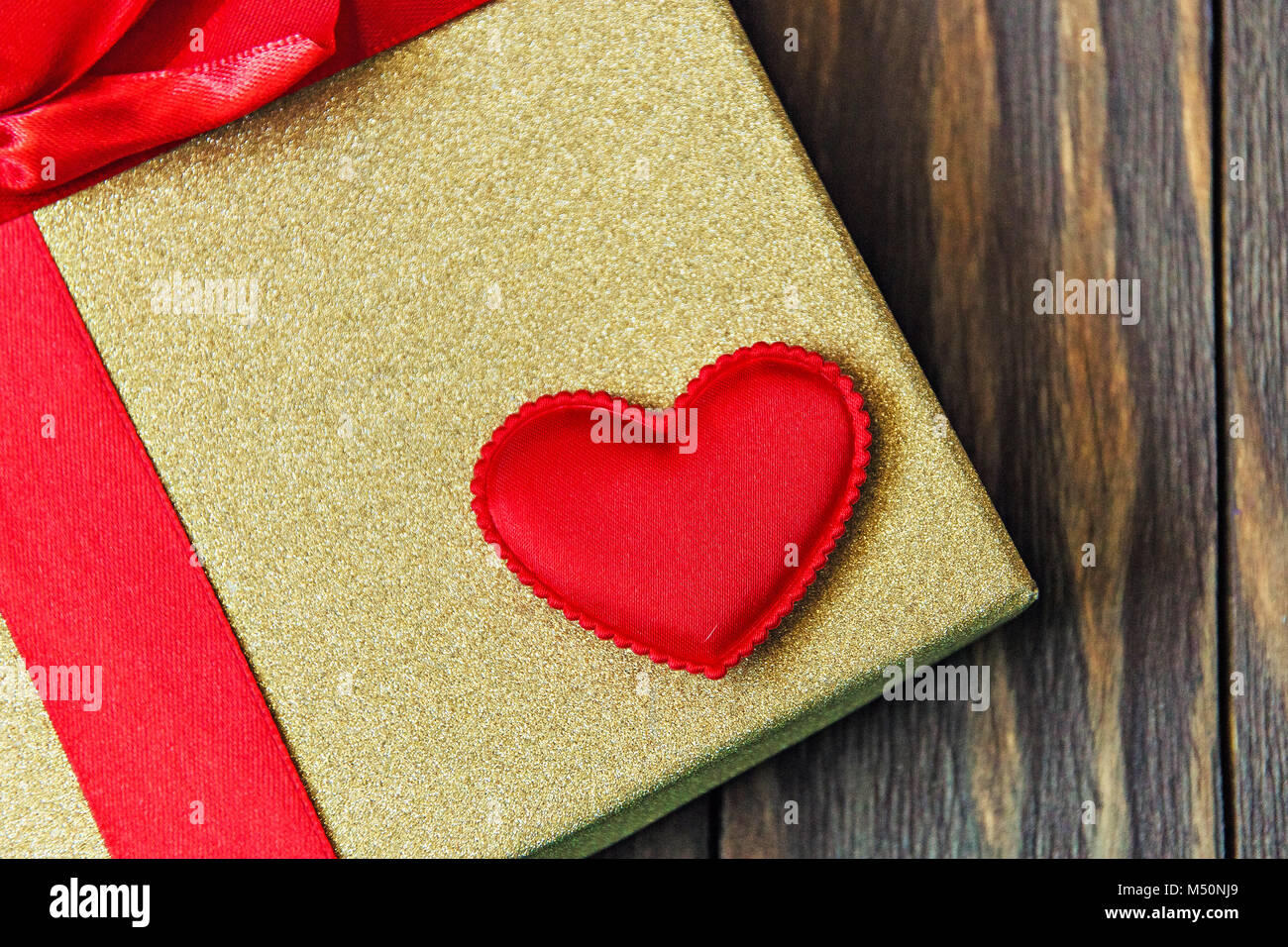 gift box with red bow and heart on wooden background. gift with love. Stock Photo