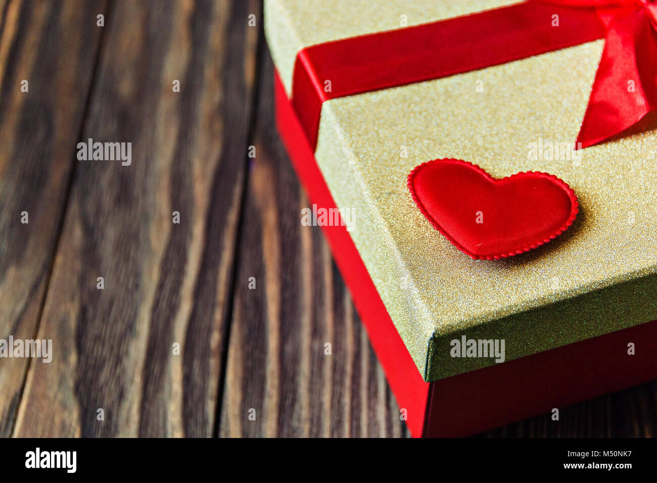 gift box with red bow and heart on wooden background. gift with love. - Stock Image