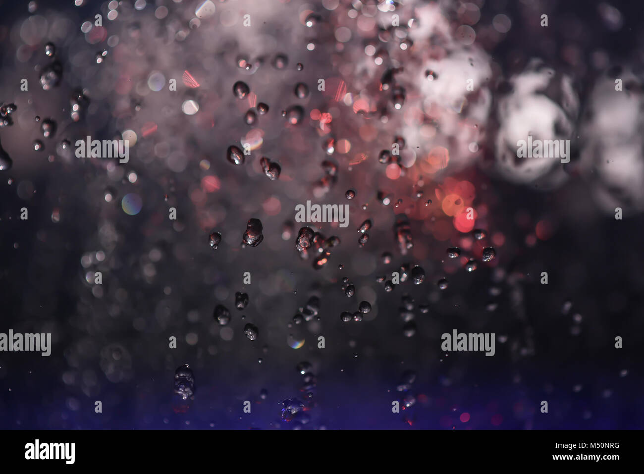 Multicolored spray fountain at night in the club - Stock Image
