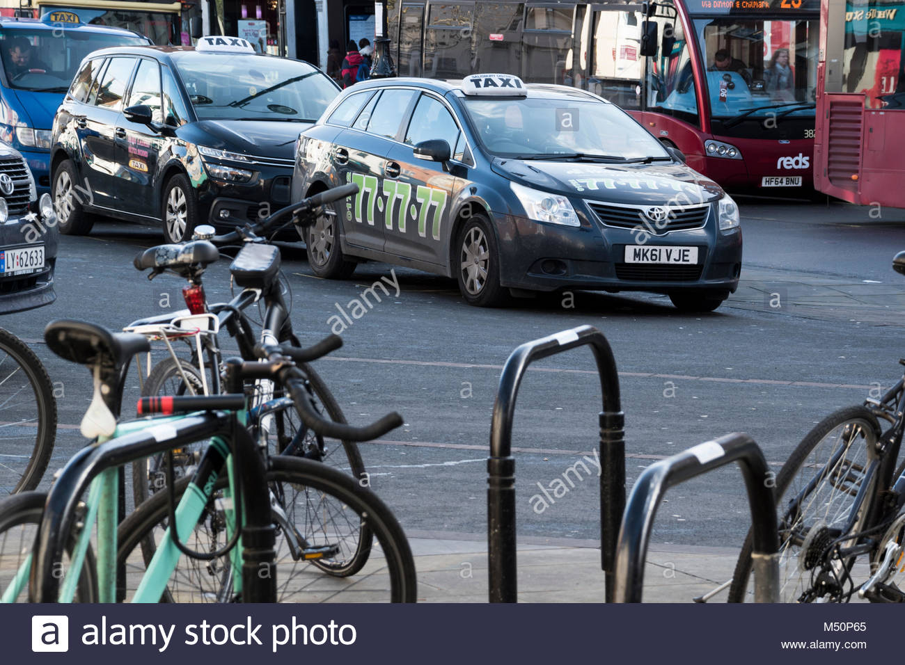 View of different types of transport - push bikes, taxi (mini) cabs with buses in the background, Salisbury, Wiltshire, Stock Photo
