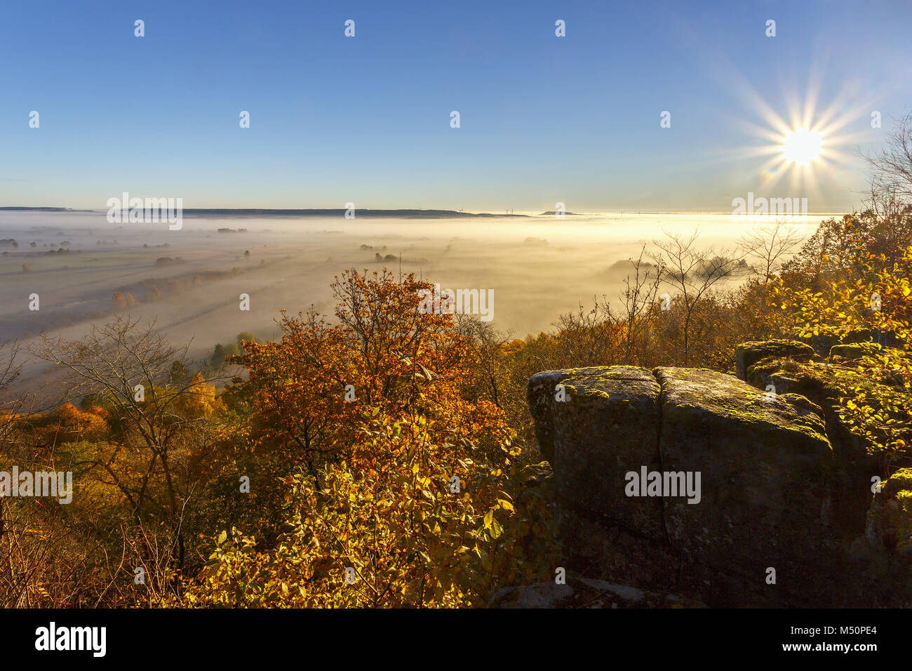 Sun shines over a valley with fog in autumn - Stock Image