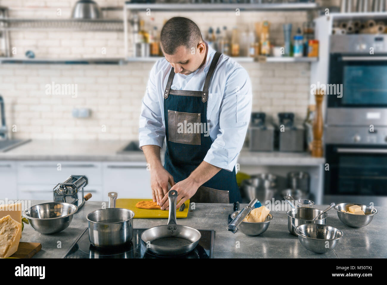 chef preparing dough for pasta on kitchen - Stock Image