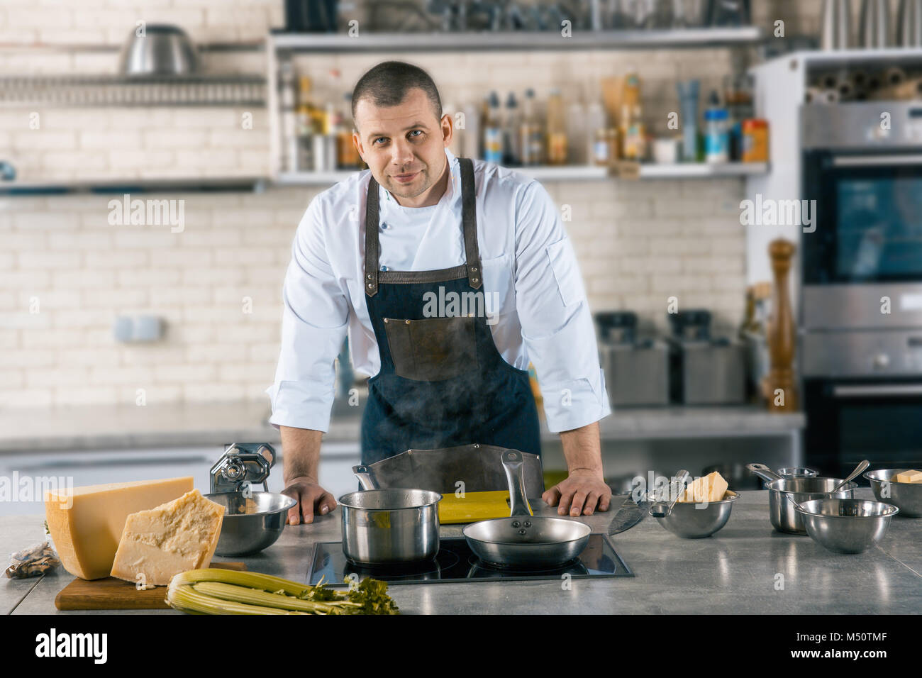 Friendly cook is situating in airy kitchen. cook preparing to cook ravioli - Stock Image