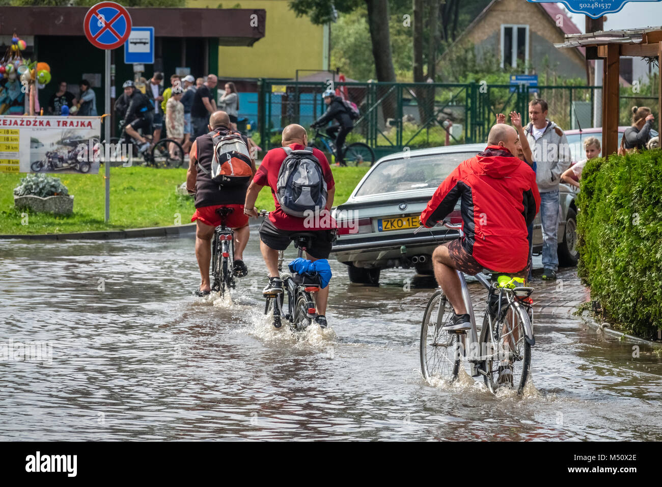 Cycling on a flooded road - Stock Image