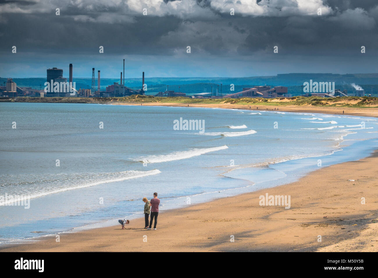 A family enjoy a beautiful beach with heavy industry in the background. - Stock Image