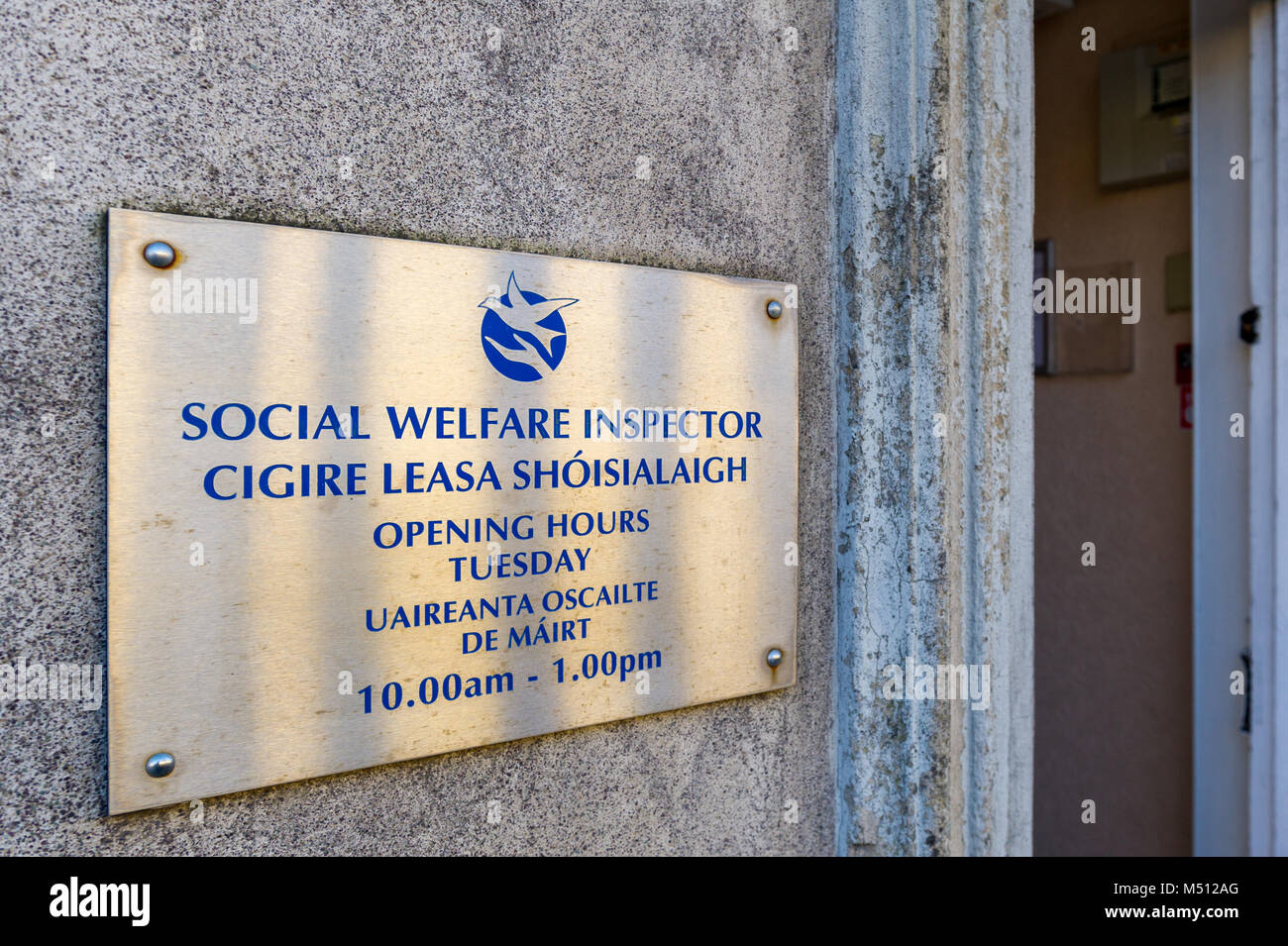 Social Welfare Inspector office opening hours sign in Dunmanway, County Cork, Ireland. - Stock Image