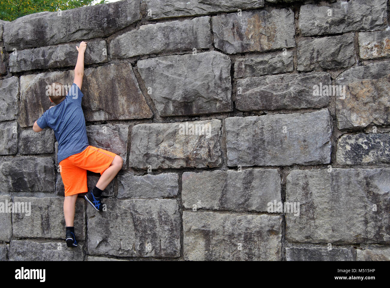 Boy climbing a Rock Wall - Stock Image