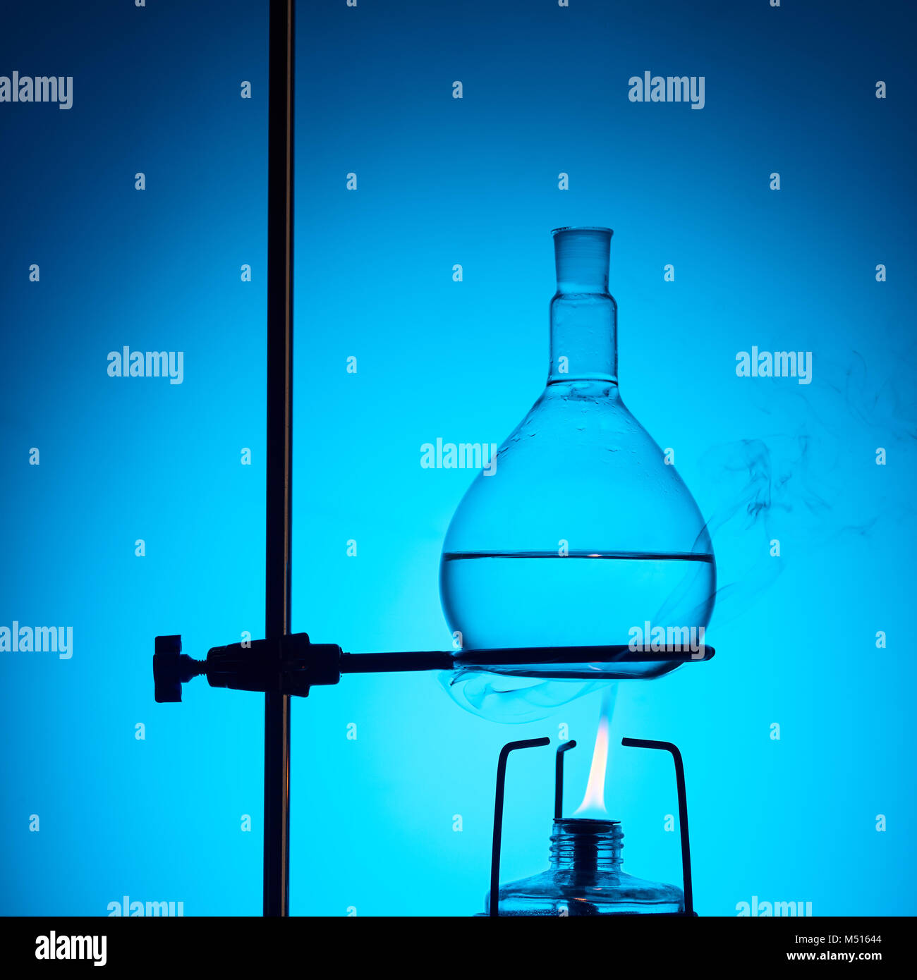 warming up liquid for chemical test isolated on blue - Stock Image
