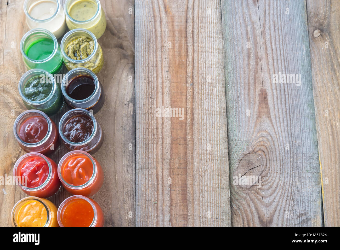 Assortment of sauces in the glass jars - Stock Image