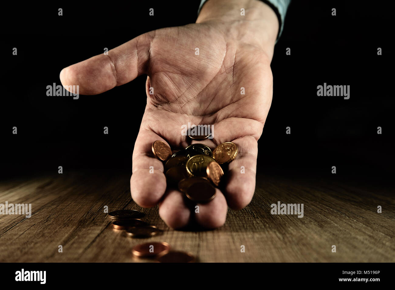 Handful of coins in the palm - Stock Image