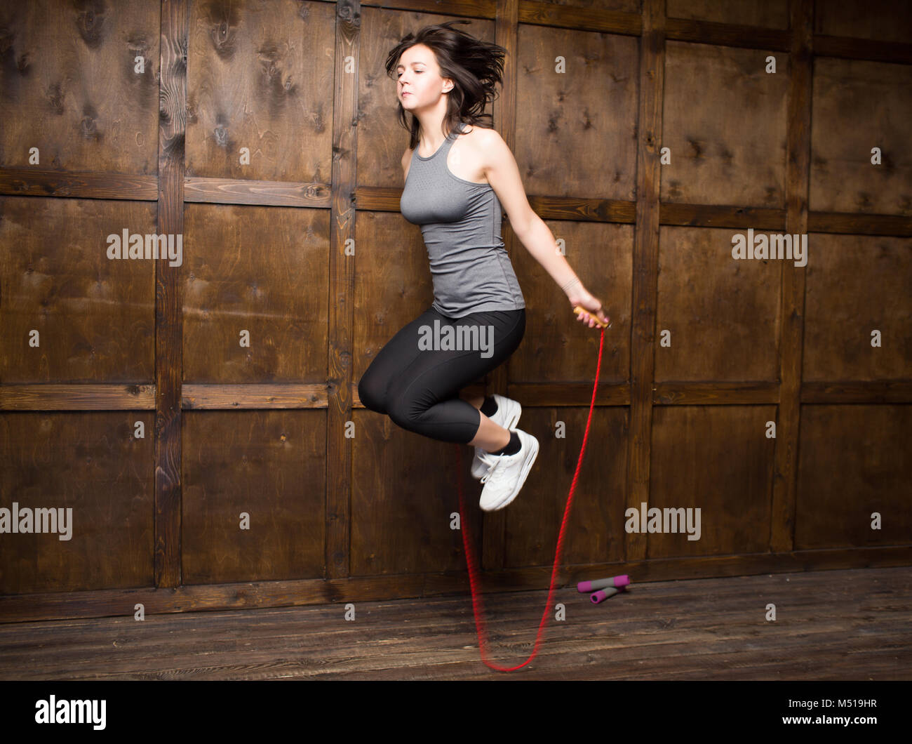 Girl jumping on skipping rope - Stock Image