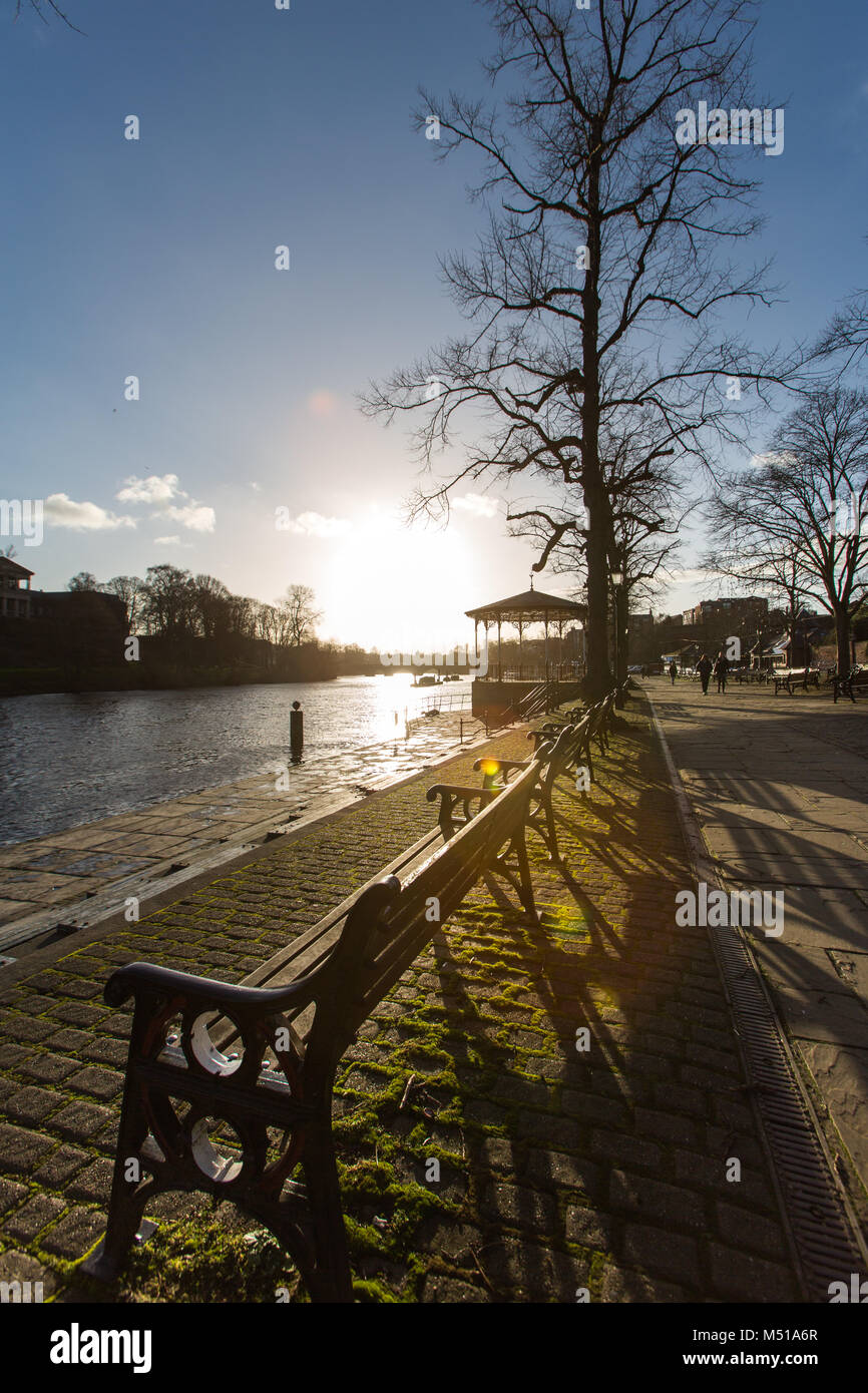 City of Chester, England. Picturesque silhouetted view of the empty benches and the Victorian bandstand on the Groves, - Stock Image