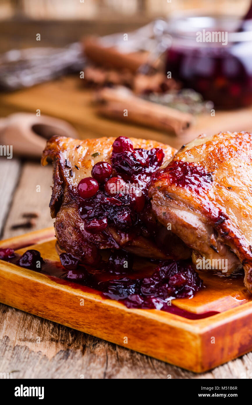 Roast chicken legs on cutting board served with cranberry sauce on rustic wooden table - Stock Image
