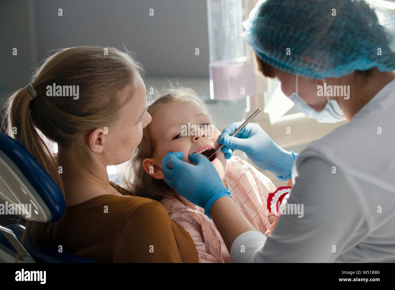 Little girl with mommy in dentist room - doctor examines the girl's teeth - Stock Image