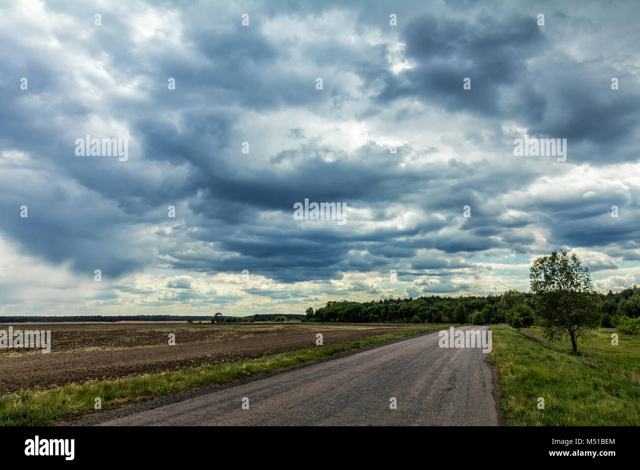 Mysterious clouds in the sky over an country road Stock Photo