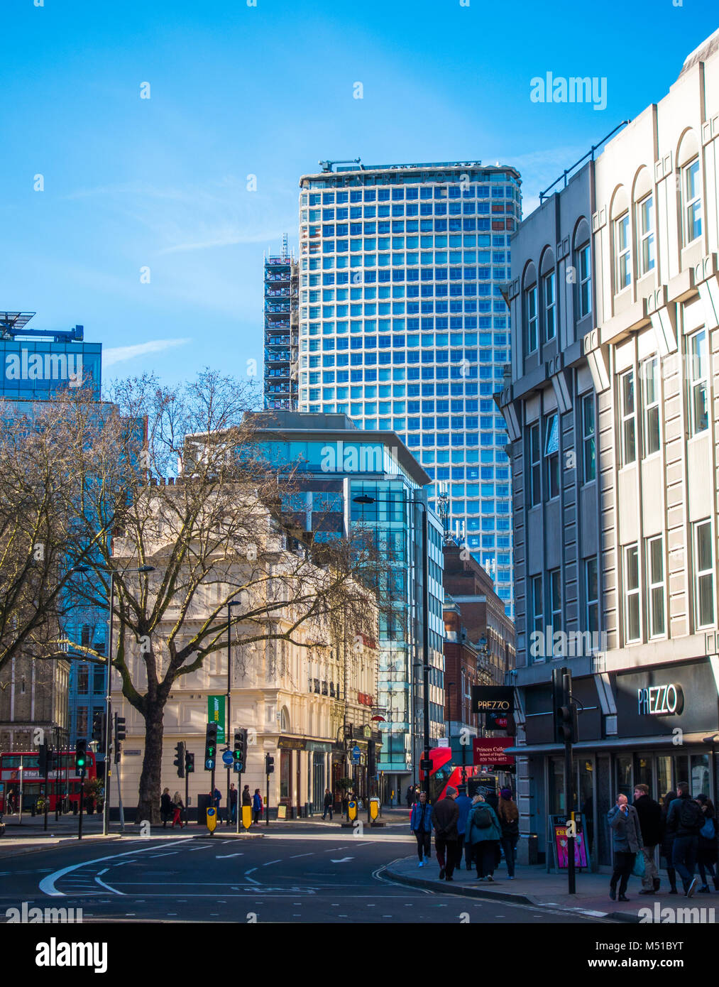 Striking mix of old and new architecture on busy New Oxford Street, with people wrapped up in warm winter clothing. - Stock Image