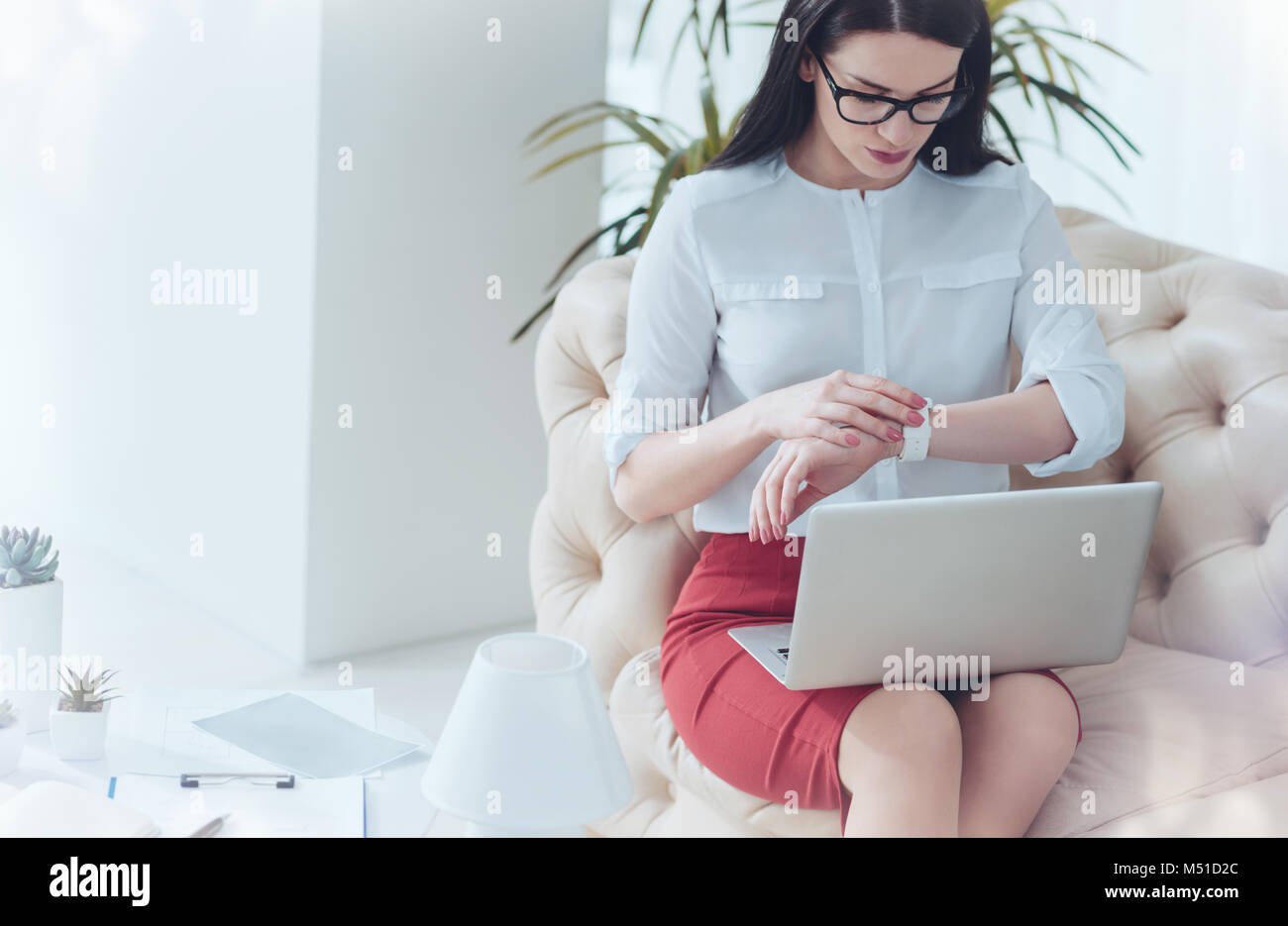 Business woman looking at wrist watch while waiting for client - Stock Image