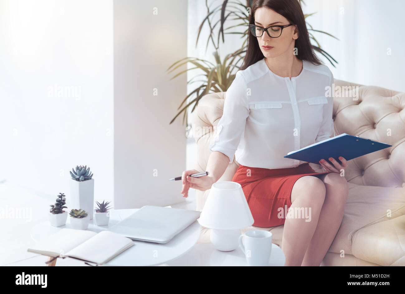 Serious businesswoman scheduling timetable for clients at office - Stock Image