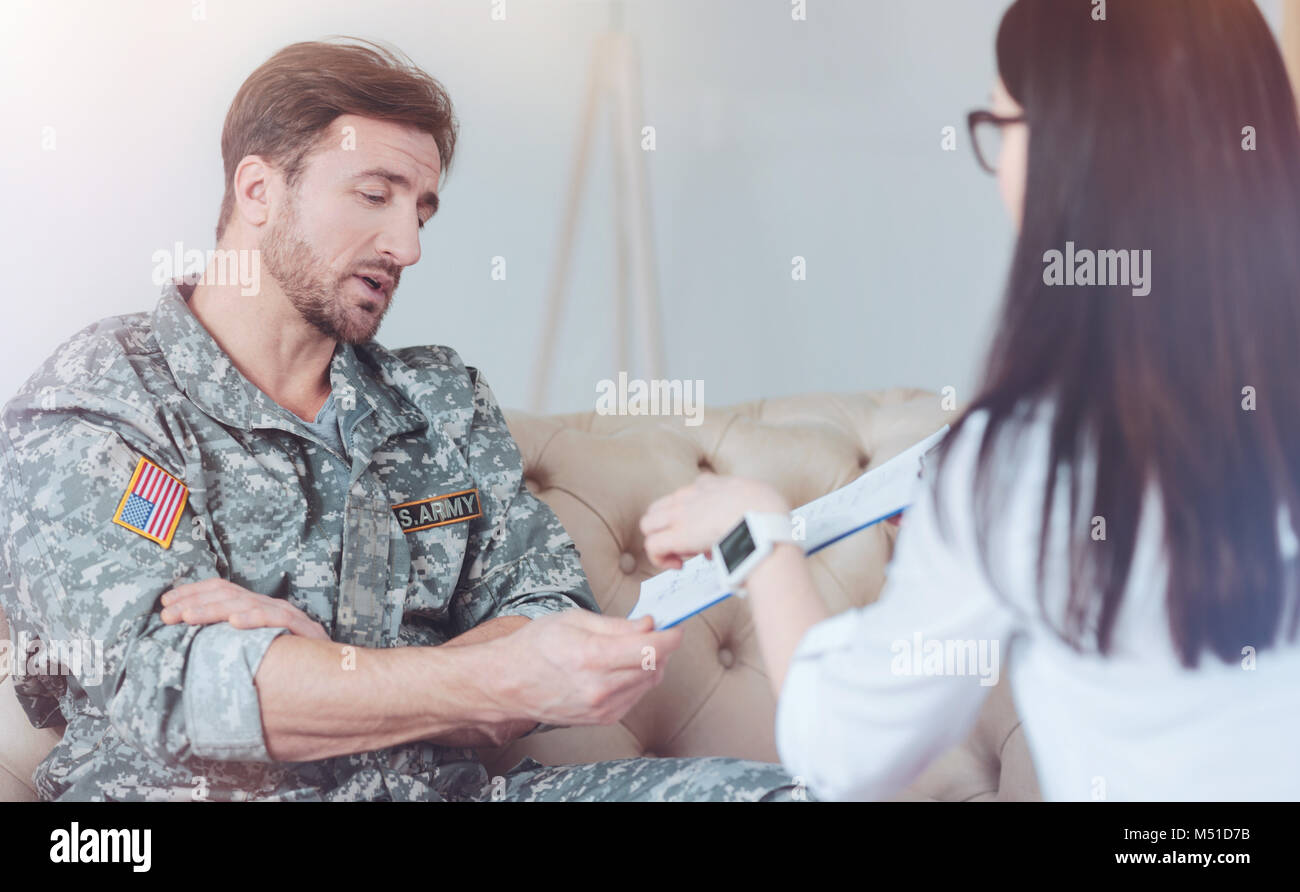Military patient talking with female psychotherapist Stock Photo