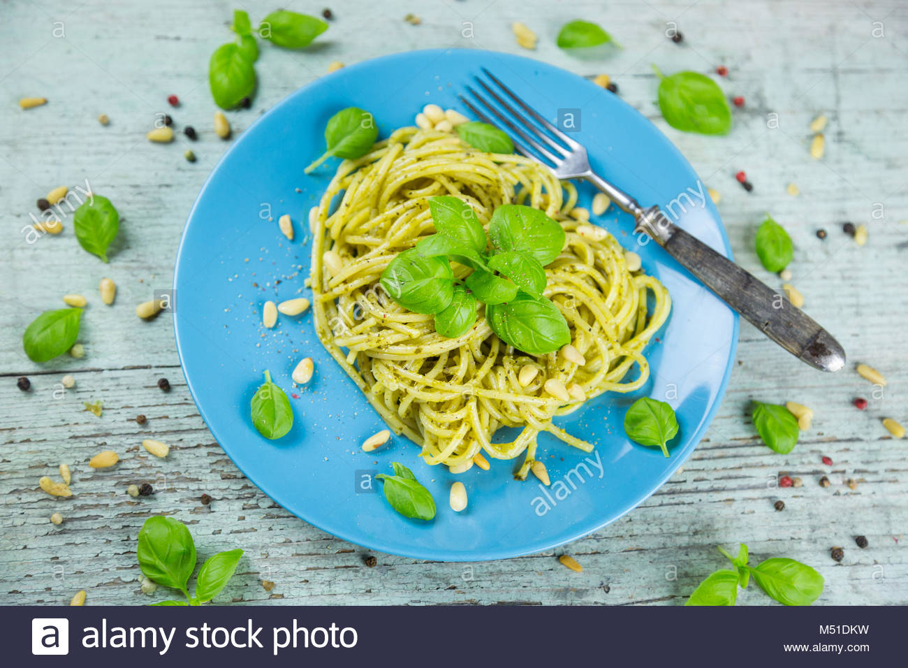 Plate of cooked spaghetti pasta with green pesto - Stock Image