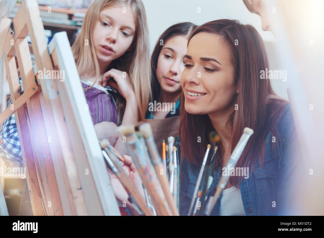 Talented kids looking at their teacher of painting working - Stock Image
