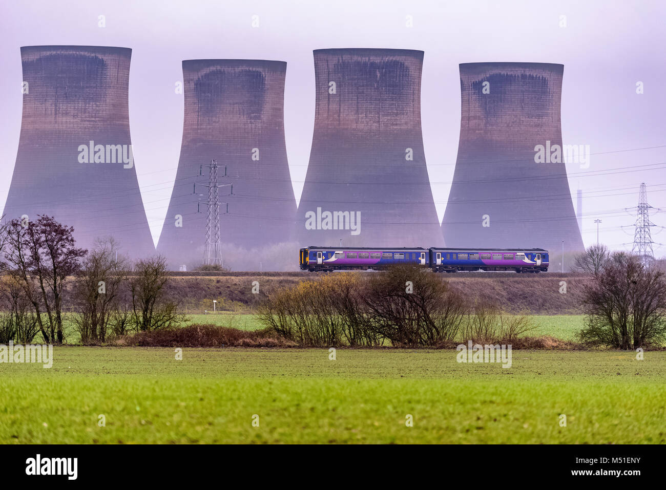 Northern Sprinter train with Fiddlers Ferry power station cooling towers in the background. - Stock Image