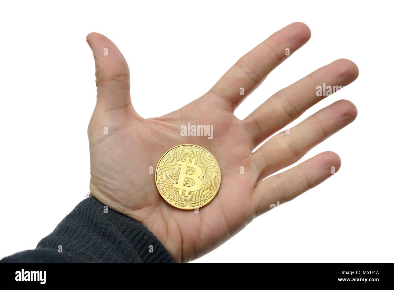 Person holding golden Bitcoin token Stock Photo