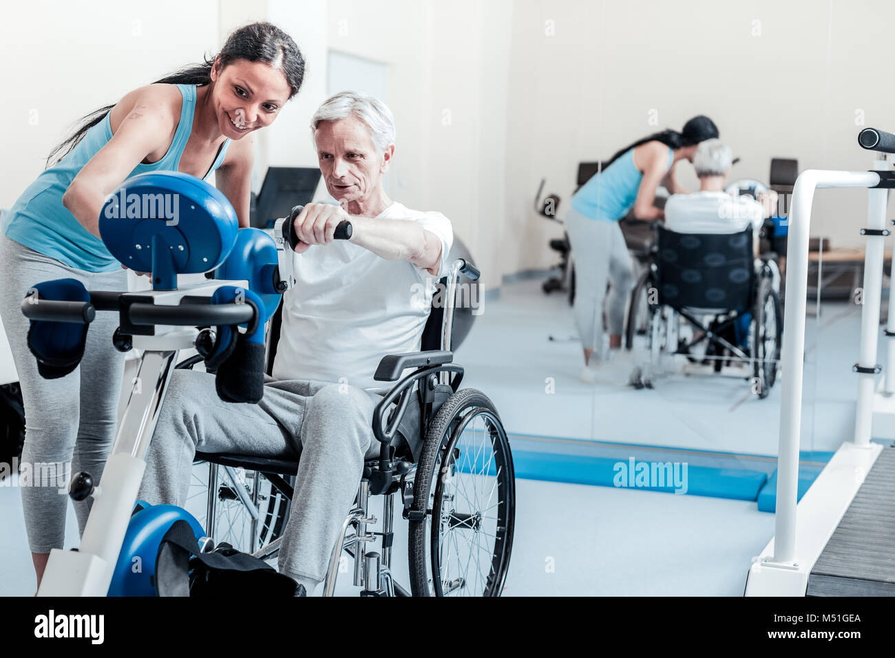 Serious old man exercising while sitting in a wheelchair - Stock Image
