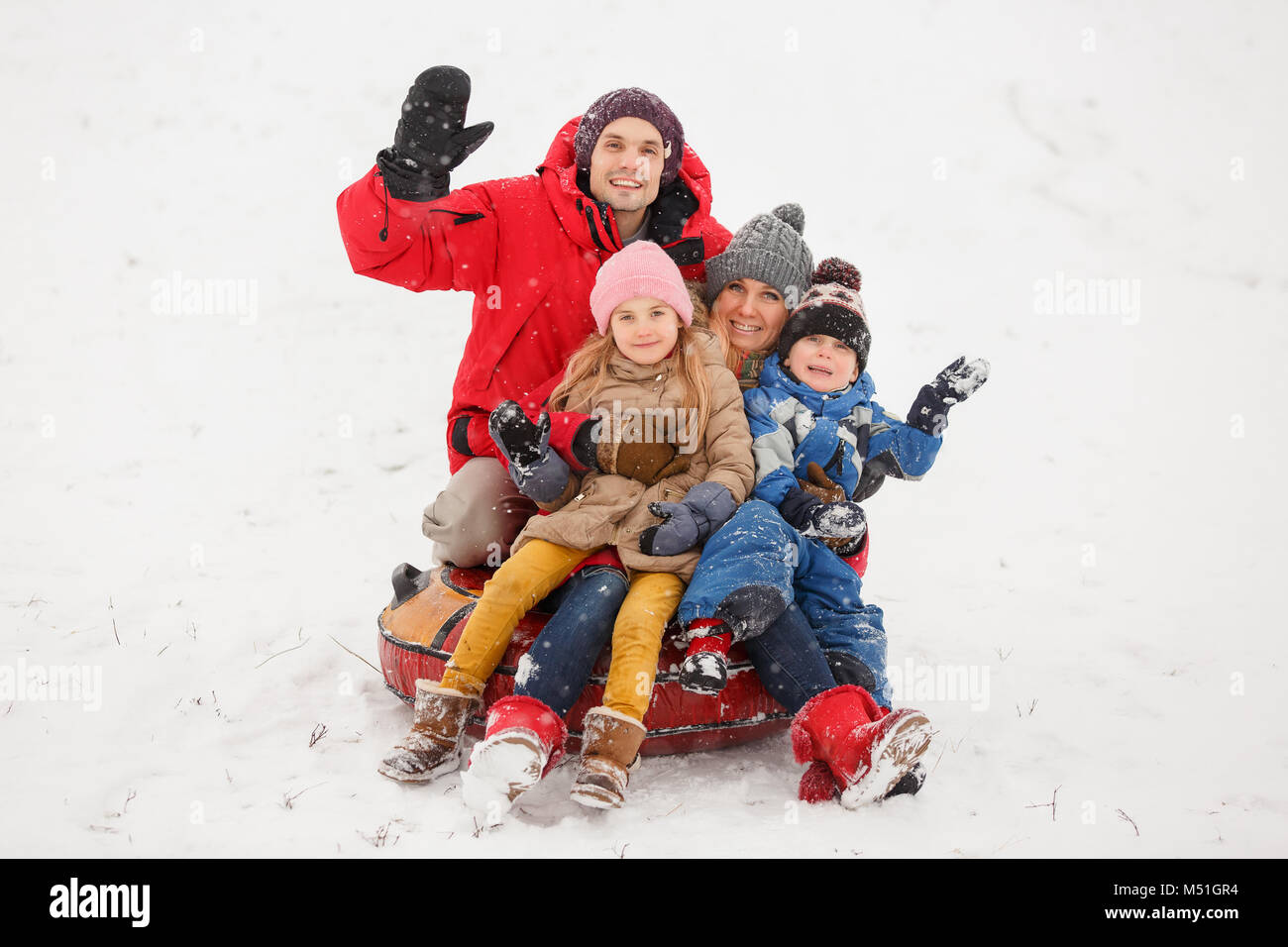 Picture of happy parents with daughter and son sitting on tubing in winter - Stock Image