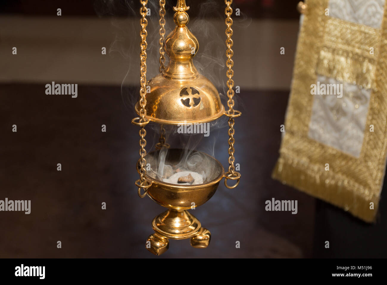 Church censer of golden color with smoke - Stock Image