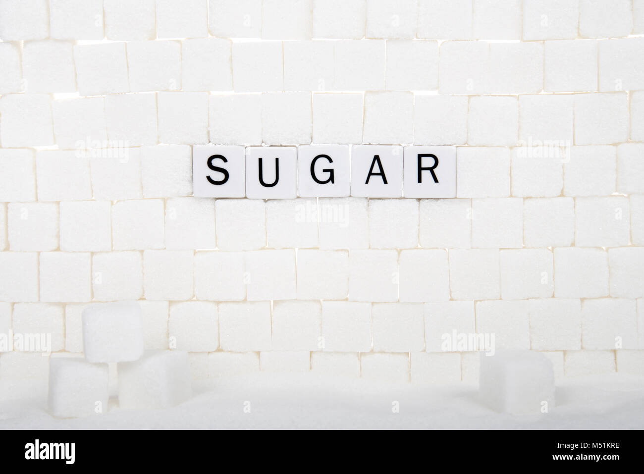 "Wall of sugar cubes with word SUGAR spelled out on some of the bricks. sugar delivers ""empty calories""  calories - Stock Image"