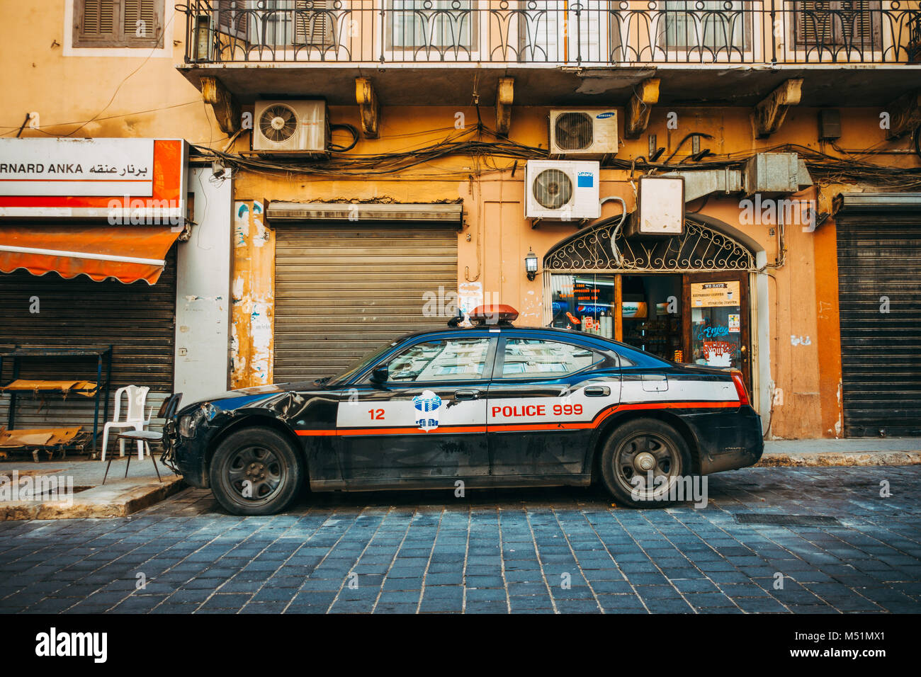 a damaged Dodge Charger Police Pursuit car sits on the roadside in Beirut, Lebanon - Stock Image