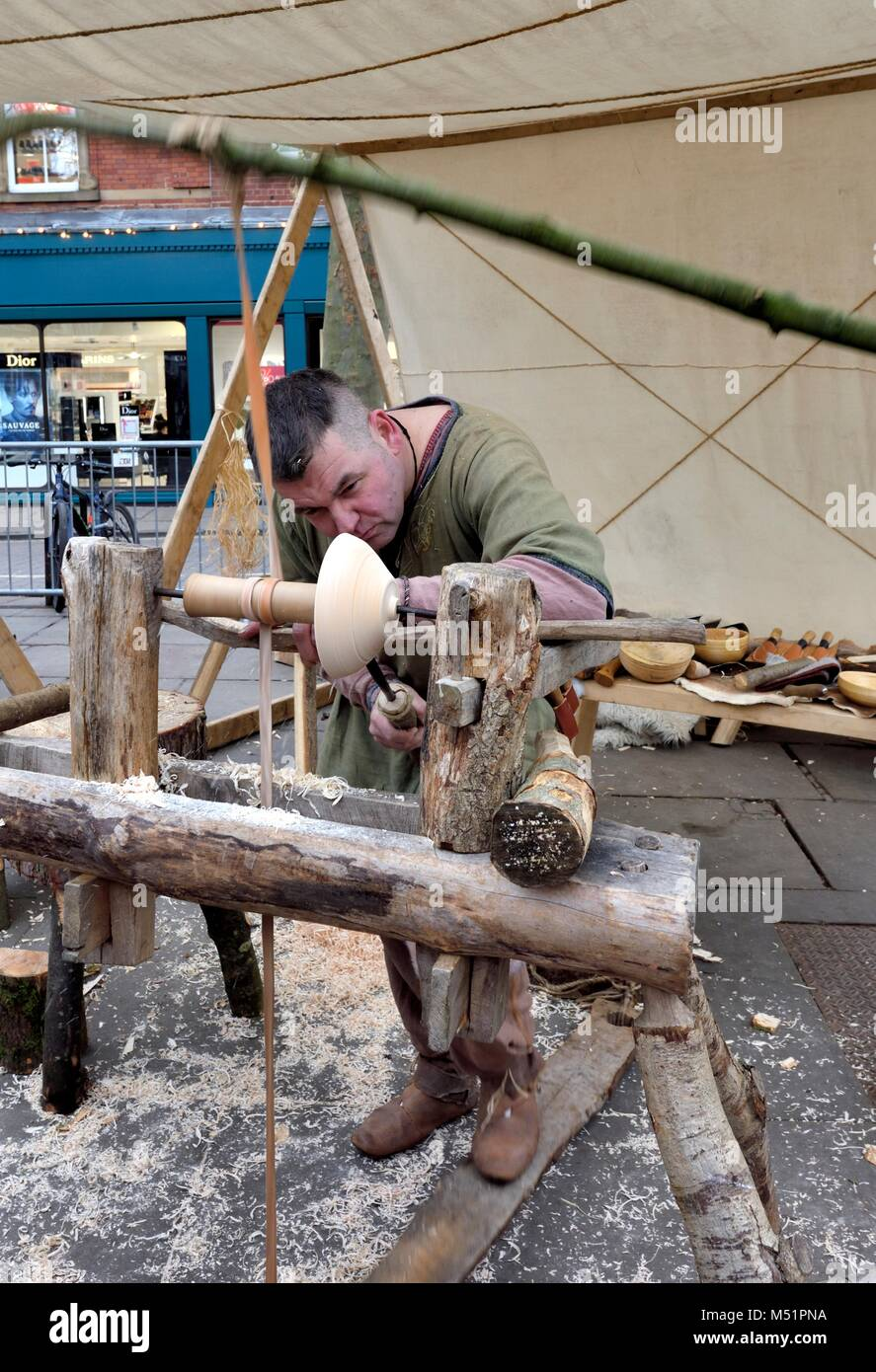 A man carving a wooden dish on a foot operated turning lathe York,North Yorkshire, England UK - Stock Image