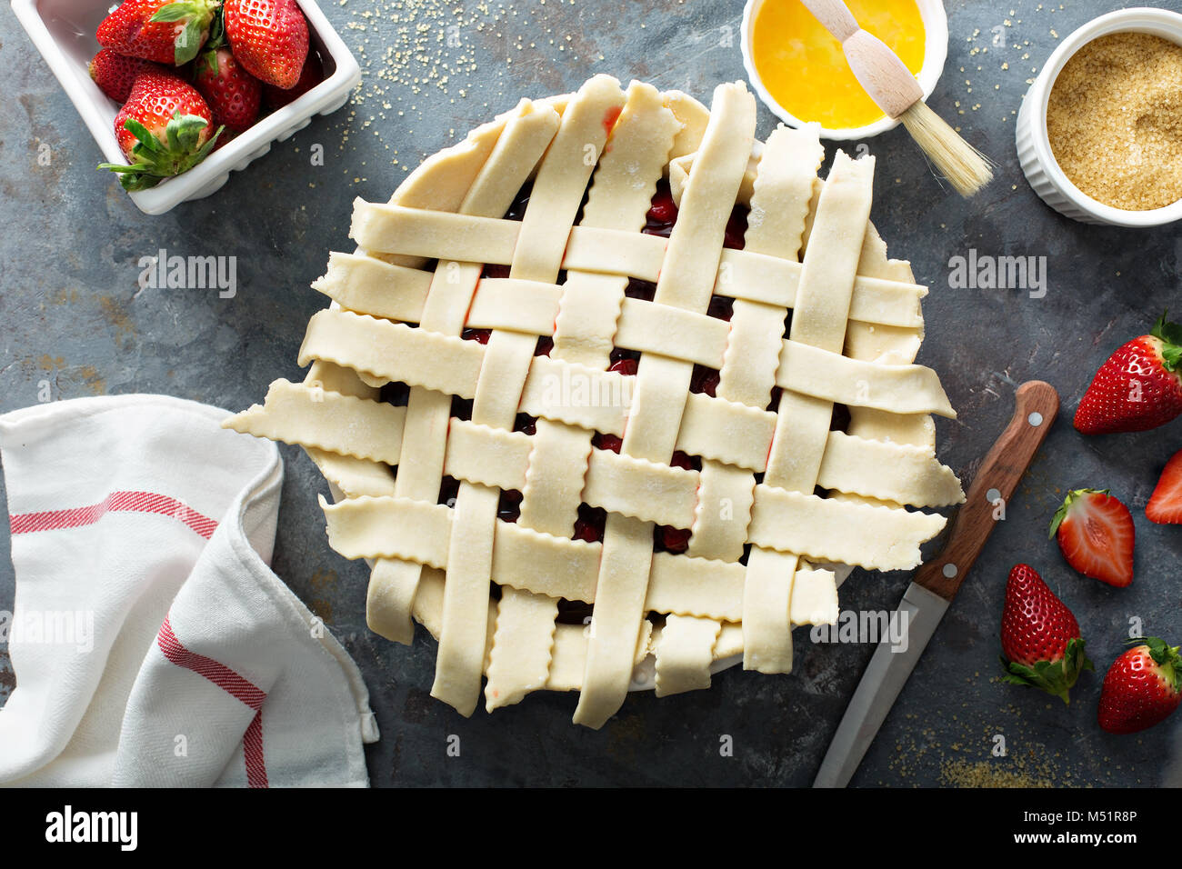 Making strawberry pie from scratch with homemade crust lattice and sweet filling - Stock Image