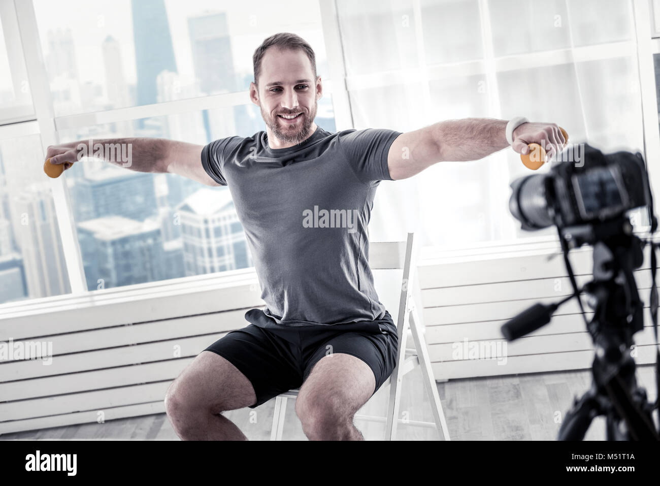 Appealing male blogger exercising with dumbbell - Stock Image