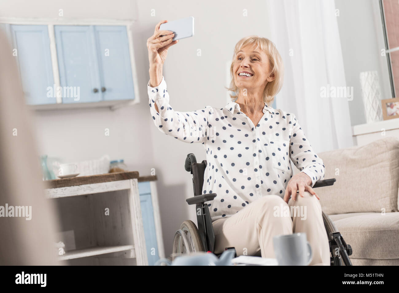 Handicapped mature woman taking selfie - Stock Image