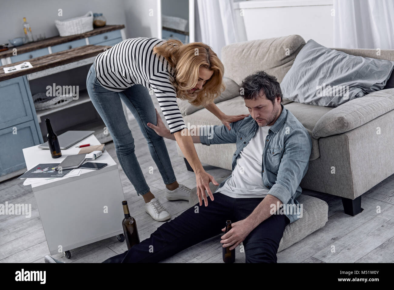 Alcohol addicted man drinking and pushing his wife - Stock Image