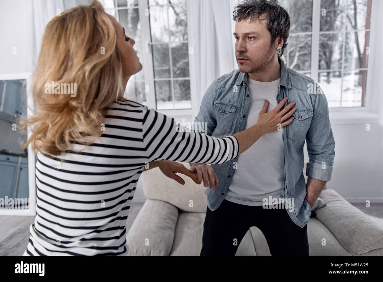 Unshaved drunk man looking at his desperate wife while talking to her - Stock Image