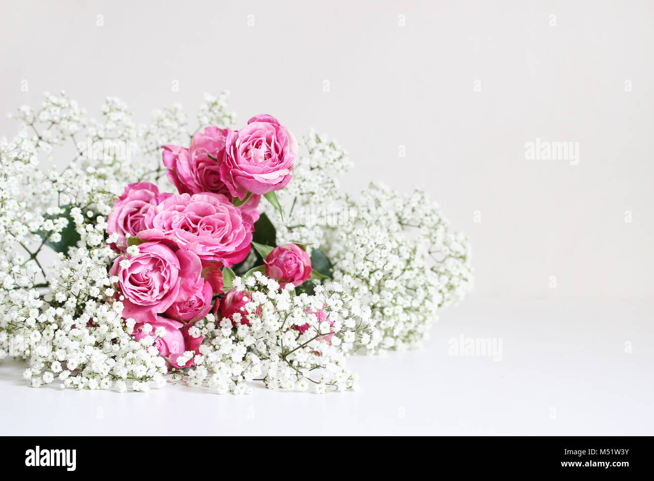 Wedding styled stock photo. Still life with pink roses and baby's breath Gypsophila flowers on white table background. Stock Photo