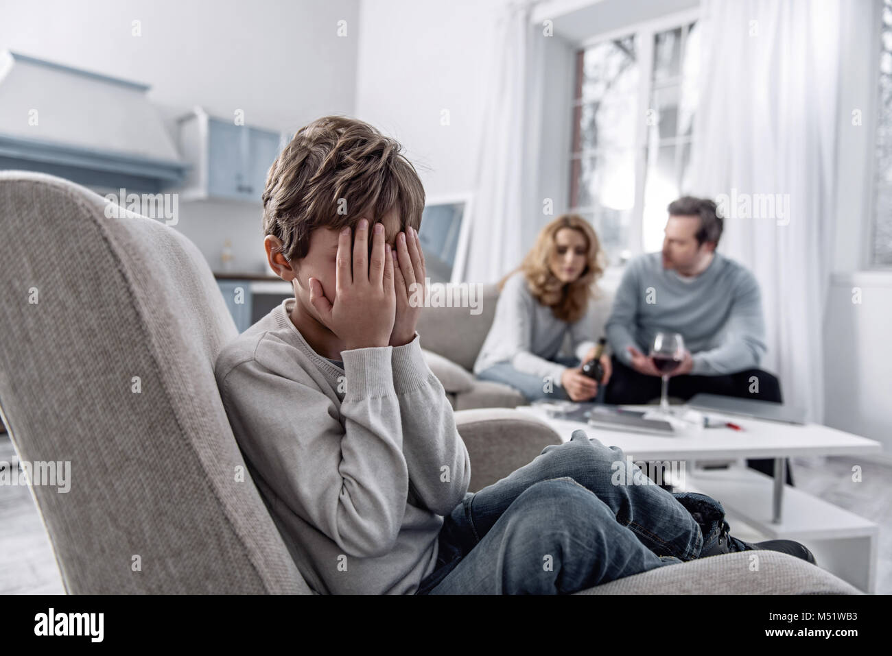 Scared boy closing his eyes while his parents having a serious talk - Stock Image