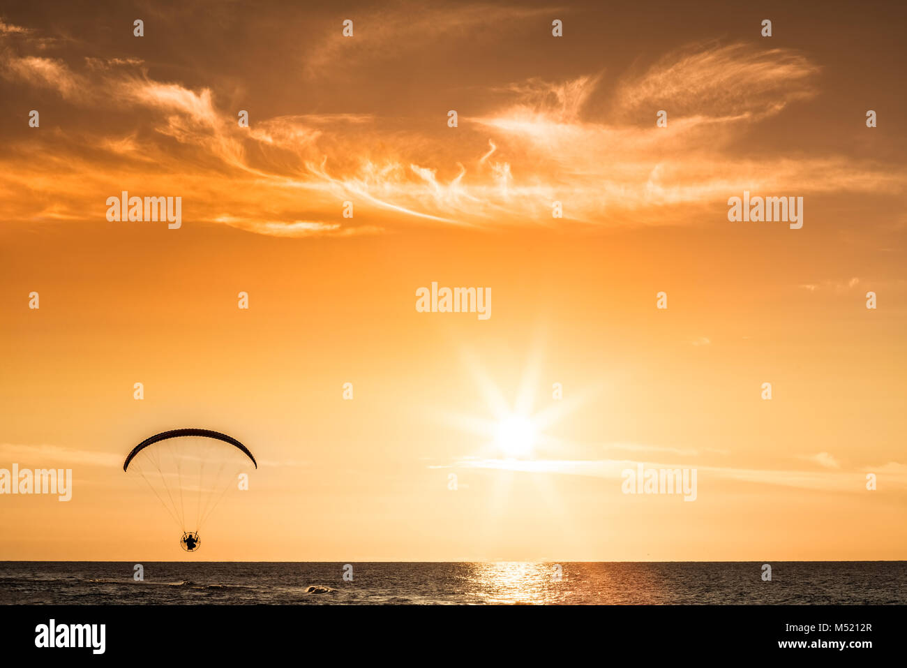 Paraglider flying at sunset - Stock Image