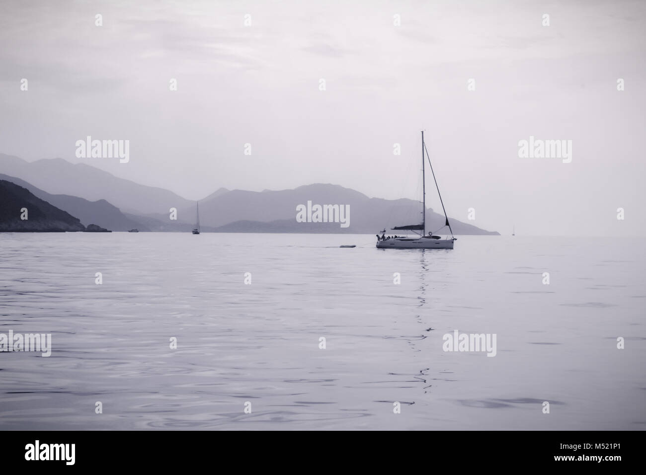 Sailing in calm seas with mountains in the distance in monotone dark grey to whiteout.  The mountains of Greece - Stock Image