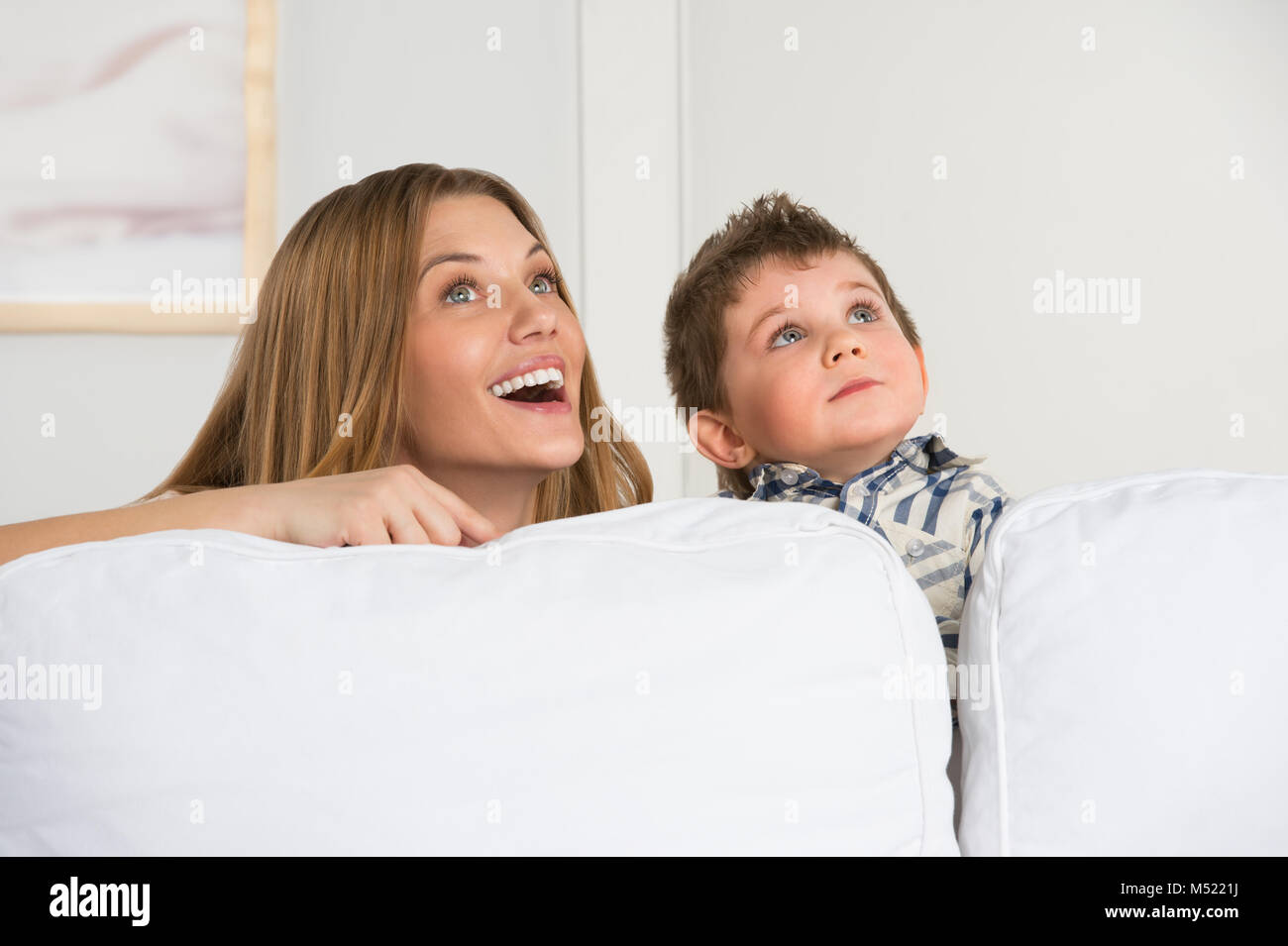 Happy young mother and her cute son playing at home and dreaming Stock Photo