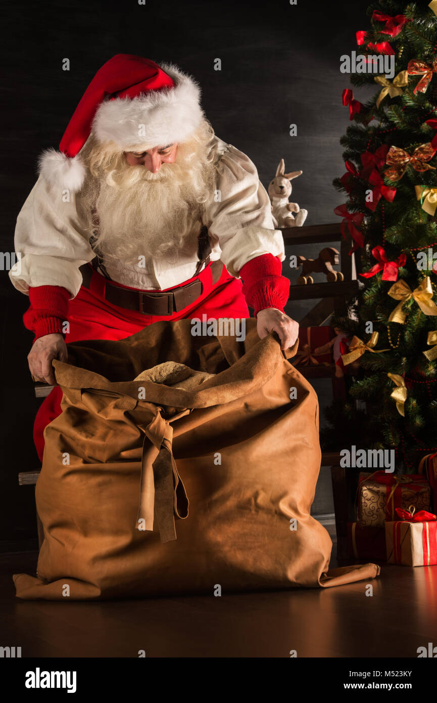 Santa Claus Opening His Sack And Taking Gifts Under Christmas Tree At Night  At Living Room At Childrenu0027s Home
