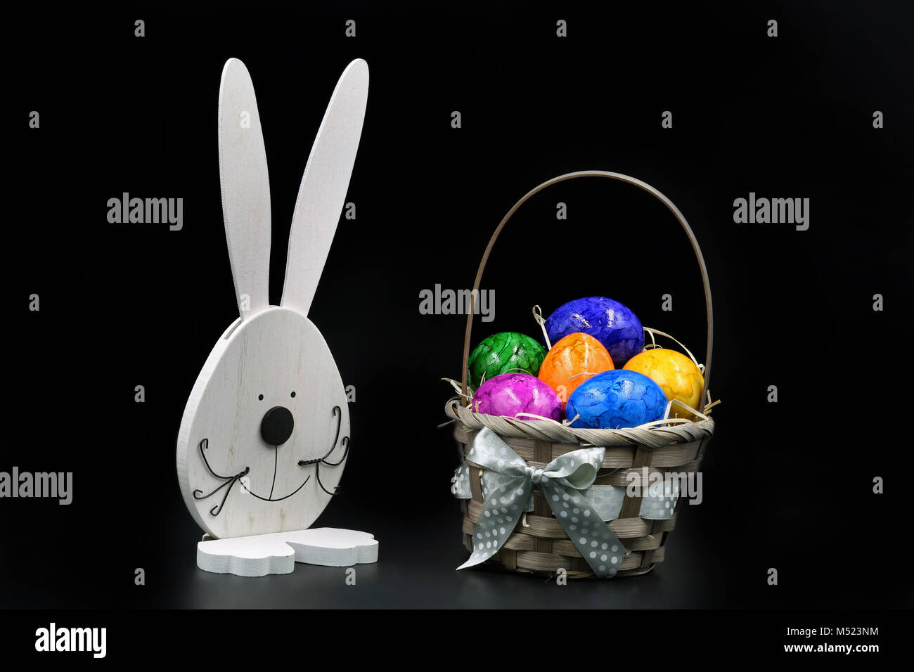Easter Eggs in Basket with rabbit isolated on black background - Stock Image