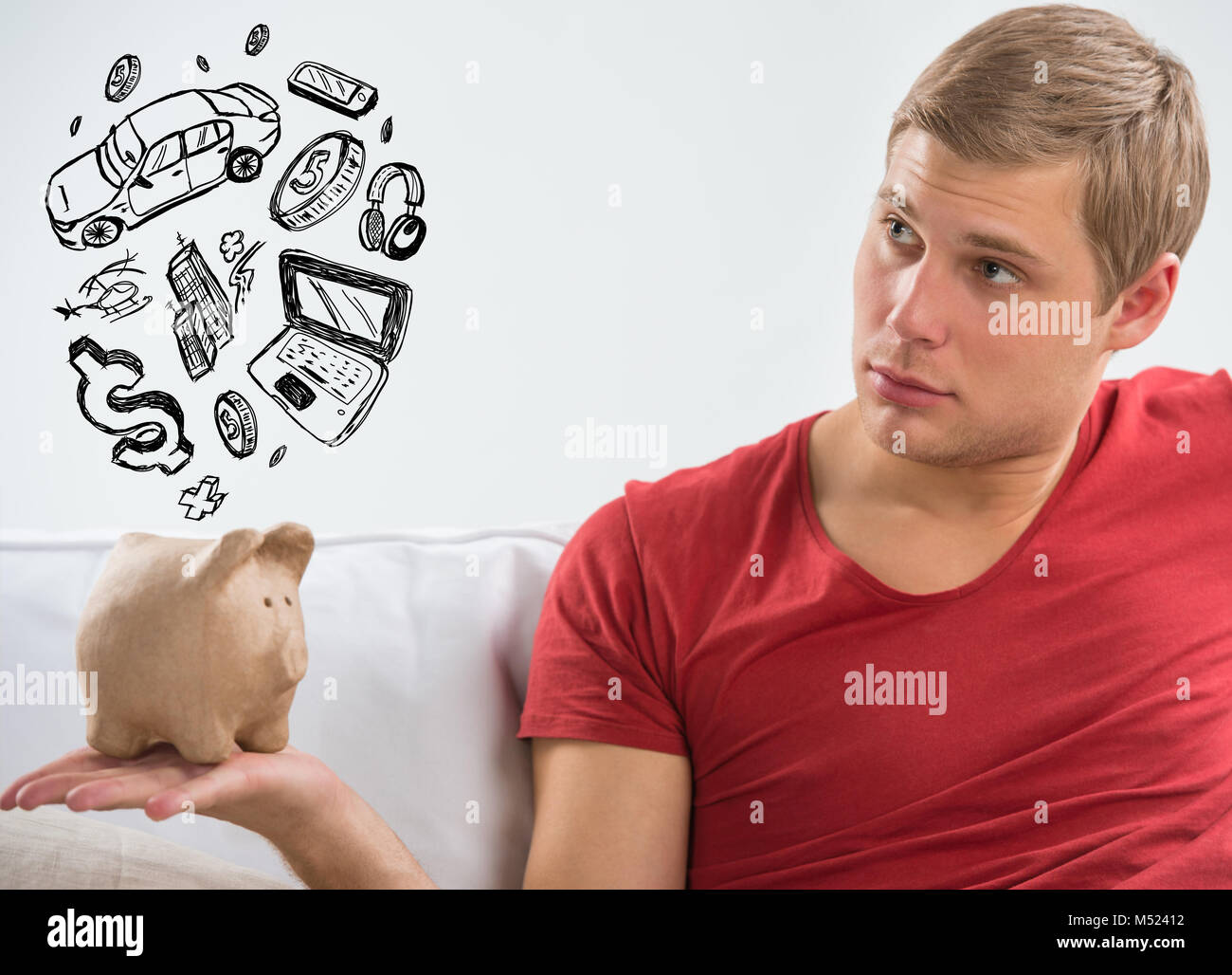 Handsome casual man with piggy bank in the living room at home. Savings concept - Stock Image