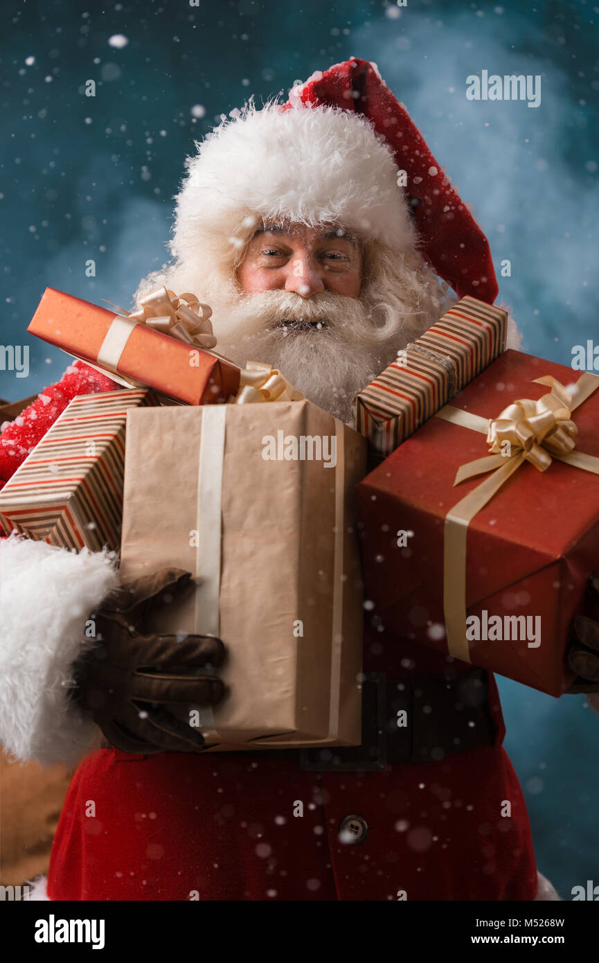 Santa Claus walking on the snow with his sack of lots of presents. Winter night with snowfall - Stock Image