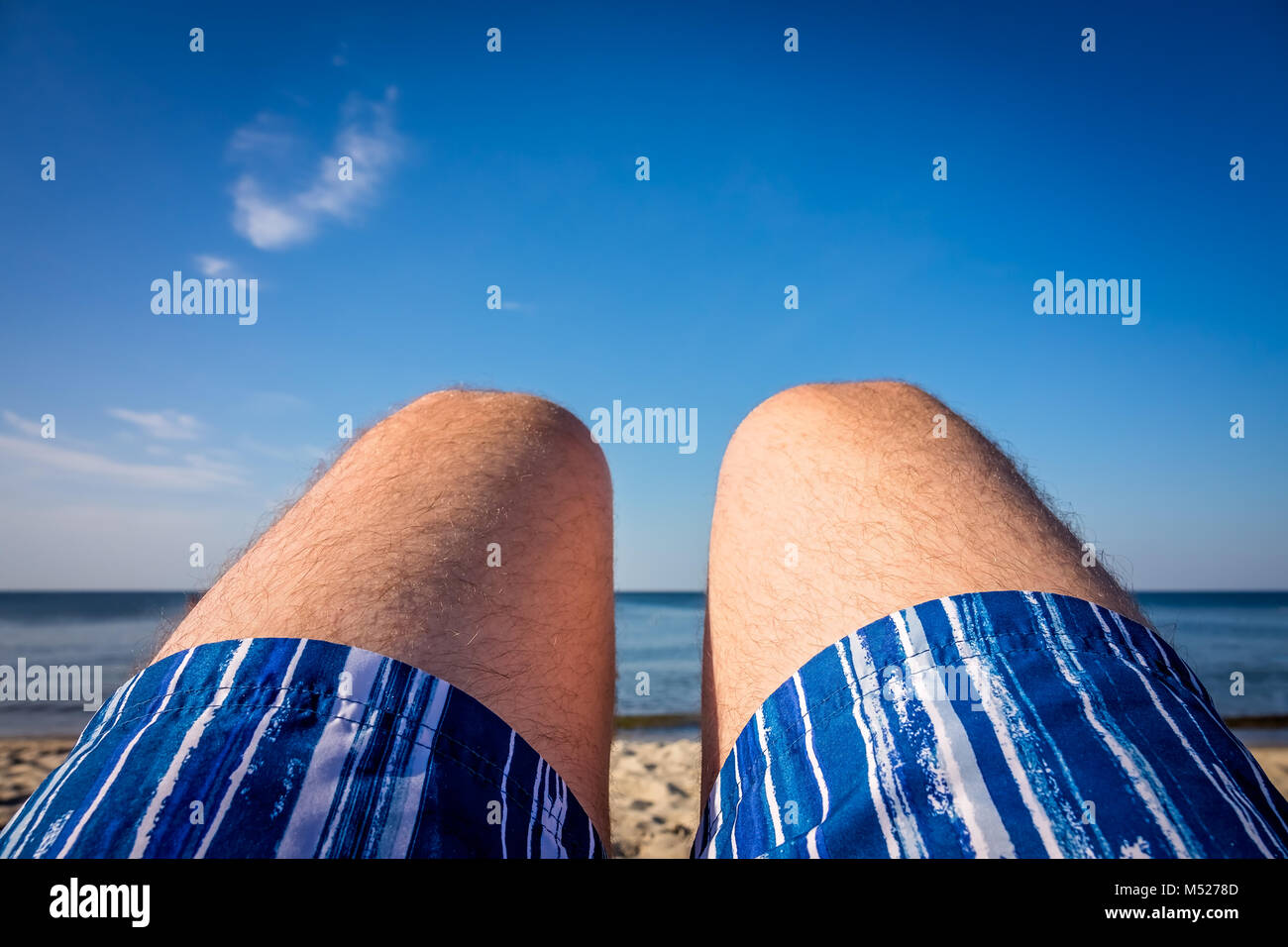 Legs of a holidaymaker on a beach - Stock Image