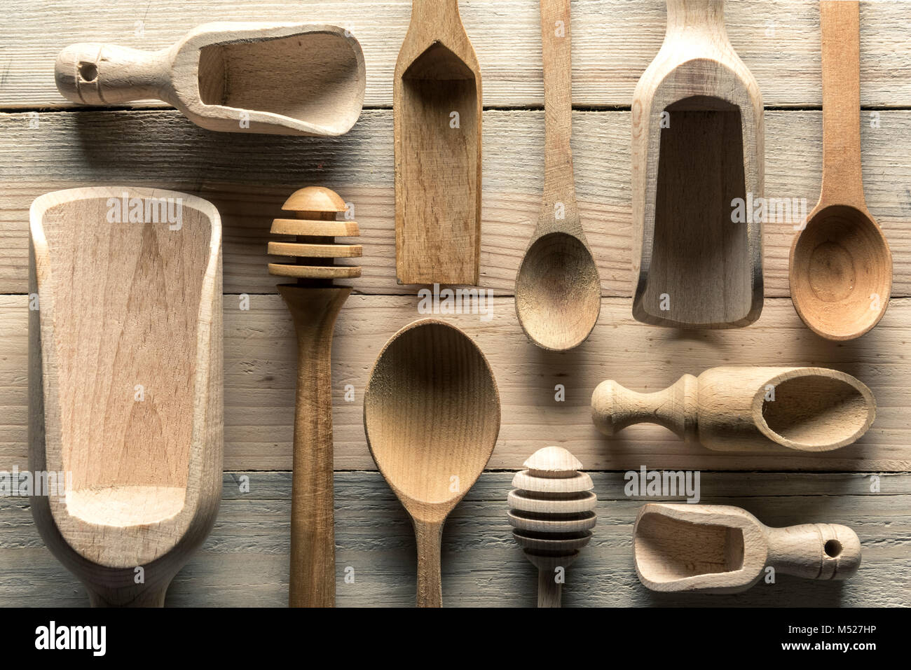 Different wooden utensils on wooden table - Stock Image