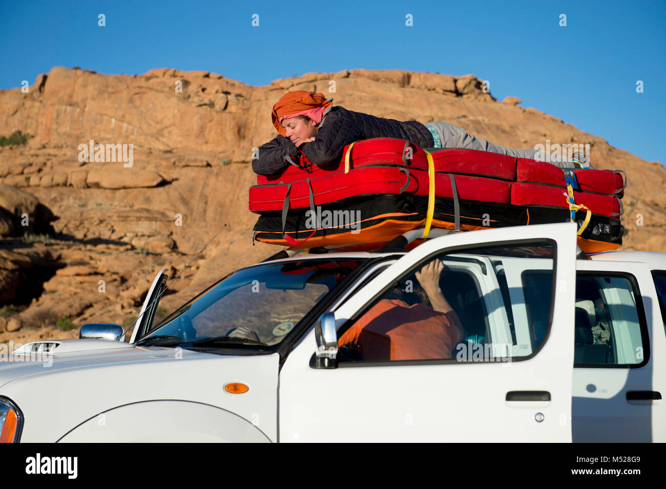 woman sleeping on crash pad on top of car during bouldering stock photo 175227593 alamy. Black Bedroom Furniture Sets. Home Design Ideas